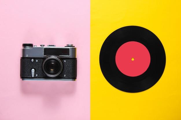 Ретро-натюрморт, 70-е гг. виниловая пластинка и пленочная камера на розово-желтом. вид сверху. плоская планировка