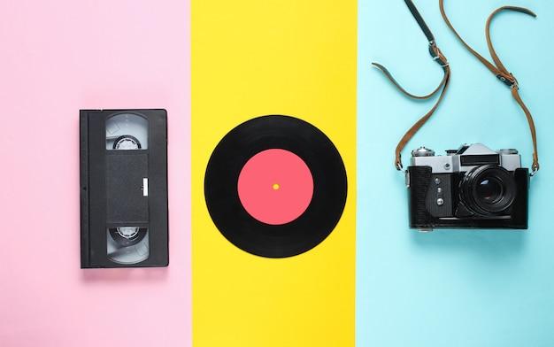 レトロな静物。ビニールレコード、ビンテージフィルムカメラ、ビデオカセット。上面図。ポップアートフラットレイアウト
