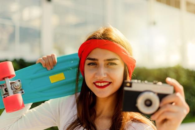 레트로 스타일. 80 년대. 밝고 화창한 날 야외에서 스케이트 보드와 필름 카메라와 함께 세련 된 옷을 입고 젊은 여자의 초상화. 유행 예쁜 젊은 여자의 여름 라이프 스타일 이미지