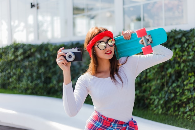 Retro style. 80s. portrait of stylish dressed young woman with skateboard and film camera outdoors on bright sunny day