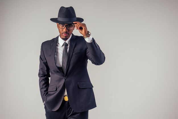 Модель афро-американского делового человека в стиле ретро в темном костюме и черной шляпе в студии на белом фоне