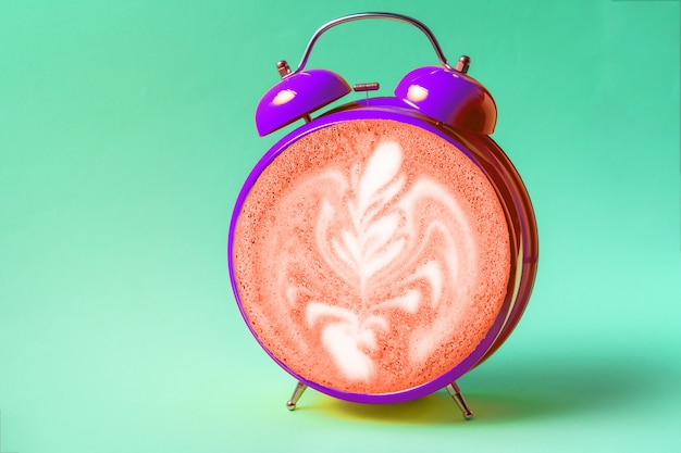 Retro style alarm clock with latte art coffee face on trendy neo mint background.