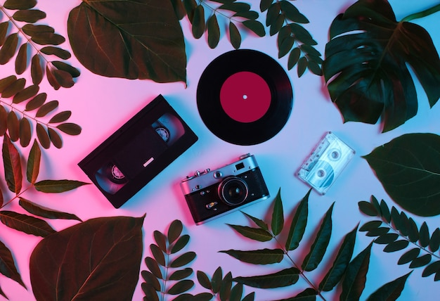 Retro style background. retro camera, vinyl record, audio cassette, vhs among green leaves on background with gradient neon blue pink light.