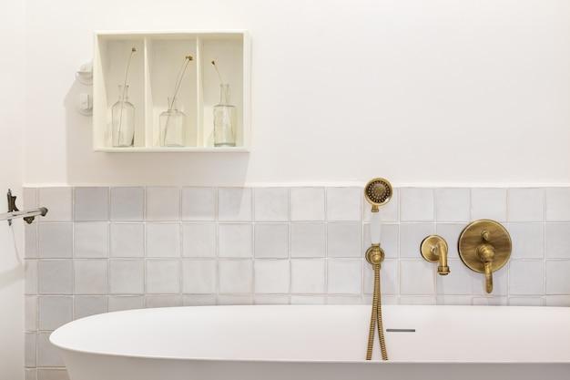 复古风格的浴室,浴缸,老式水龙头和青铜头淋浴器