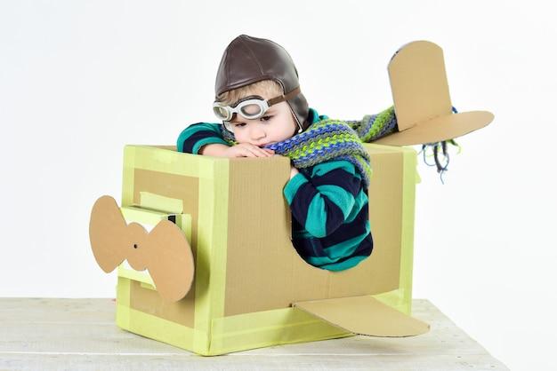 Retro style cardboard. little cute boy playing with a cardboard airplane.