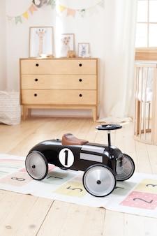 子供部屋でレトロなスタイルの子供のレーシングカー。男の子のためのレースカーの黒のビンテージモデル。魅力的な遊び場に最適な車。赤ちゃん用の輸送機器。幼稚園の子供のおもちゃの車。