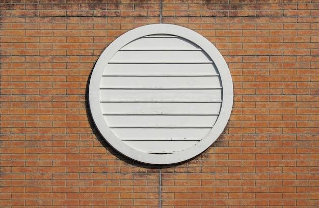Retro style circle design window on aged brick block wall background.