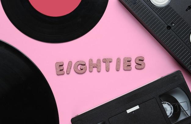 레트로 스타일 개념, 80 년대. 나무 편지에서 80 년대라는 단어가있는 분홍색의 비디오 카세트 및 비닐 레코드