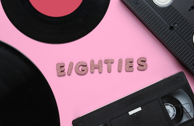 Retro style concept, 80s. video cassette and vinyl records on pink with the word eighties from wooden letters