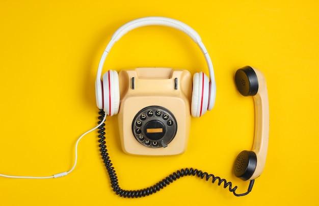 レトロなスタイルのクリエイティブなフラットレイ。黄色の背景に古典的な白いイヤホンを備えたロータリーヴィンテージ電話。ポップカルチャー。