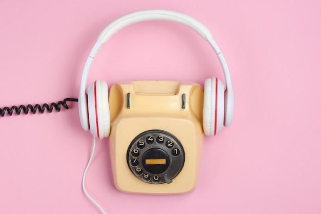レトロなスタイルのクリエイティブなフラットレイ。ピンクの背景に古典的な白いイヤホンとロータリーヴィンテージ電話。ポップカルチャー。