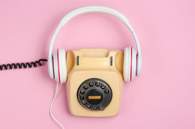 Retro style creative flat lay. rotary vintage telephone with classic white earphones on pink background. pop culture.