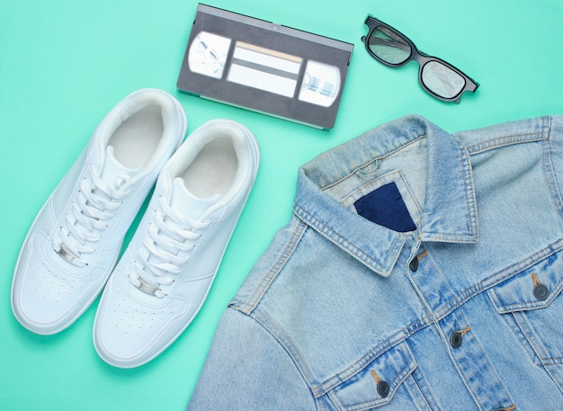 Retro style denim stylish jacket, video cassette, 3d glasses and white hipster sneakers on a mint-colored paper