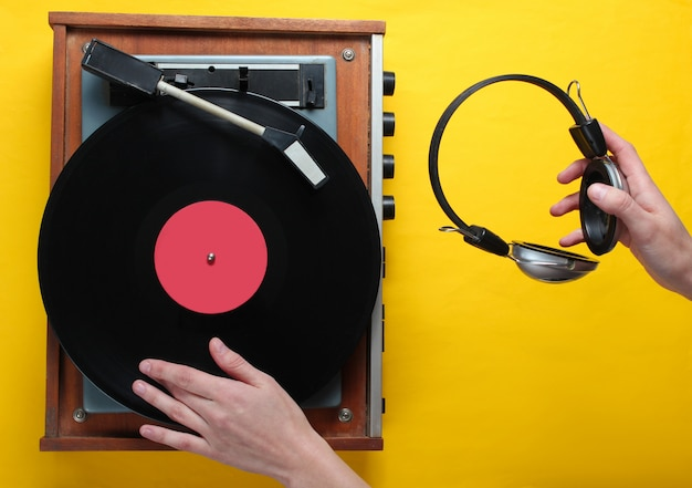 Retro style, dj plays vinyl record player and holds headphones in hand, minimalism, top view on yellow background