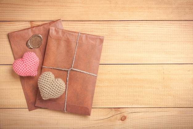 Retro style envelopes and crochet hearts on wooden background