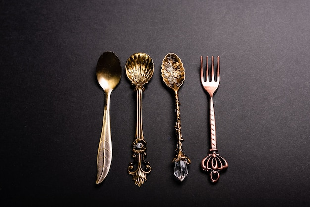 Retro style luxury cutlery on a black background, clean spoons and forks.
