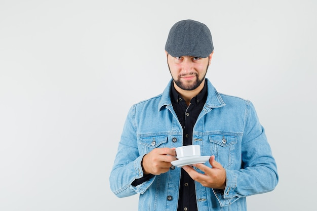 Retro-style man holding cup in jacket,cap,shirt and looking satisfied , front view.