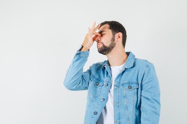 Человек в стиле ретро, держащий руку на носу в куртке, футболке и неловко выглядящий.