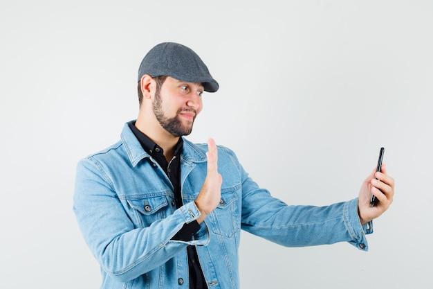 Мужчина в стиле ретро в куртке, кепке, рубашке показывает жест прощания, делая видеозвонок и уважительно выглядит, вид спереди.