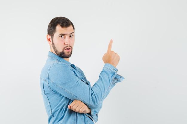 Человек в стиле ретро в куртке, футболке, направленной вверх и сосредоточенной, вид спереди.
