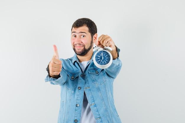 Человек в стиле ретро в куртке, футболке показывает палец вверх, держа часы и выглядит довольным, вид спереди.
