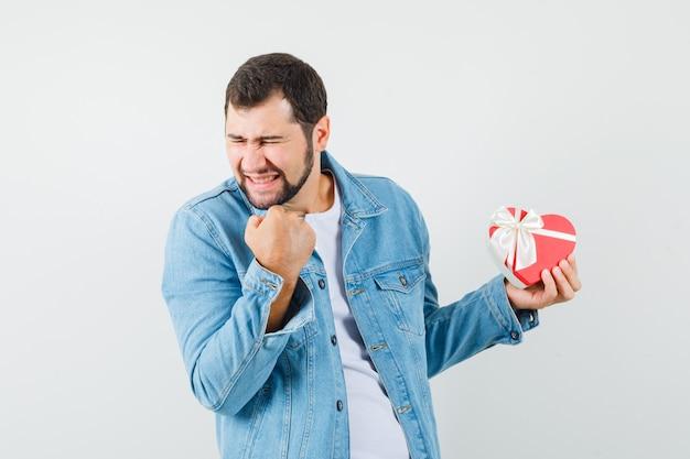 ジャケットを着たレトロなスタイルの男性、ギフトを持って陽気に見える間、勝者のジェスチャーを示すtシャツ、正面図。