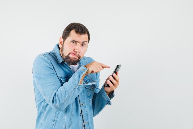 재킷에 복고풍 스타일의 남자, 전화의 화면을 터치하고 집중, 정면보기를 보면서 혀를 치는 티셔츠.