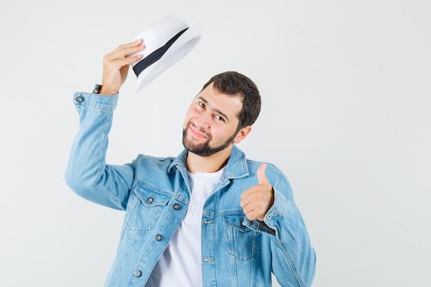재킷에 레트로 스타일의 남자, 엄지 손가락을 보여주는 동안 그의 모자를 벗고 t- 셔츠 기쁘게 찾고, 전면보기.