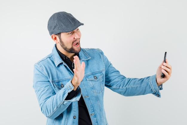 Retro-style man in jacket,cap,shirt showing goodbye gesture while making video call and looking merry , front view.