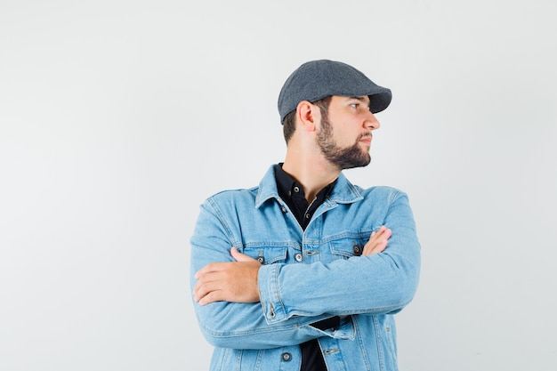 Retro-style man in jacket,cap standing with crossed arms while looking aside and looking careful , front view.