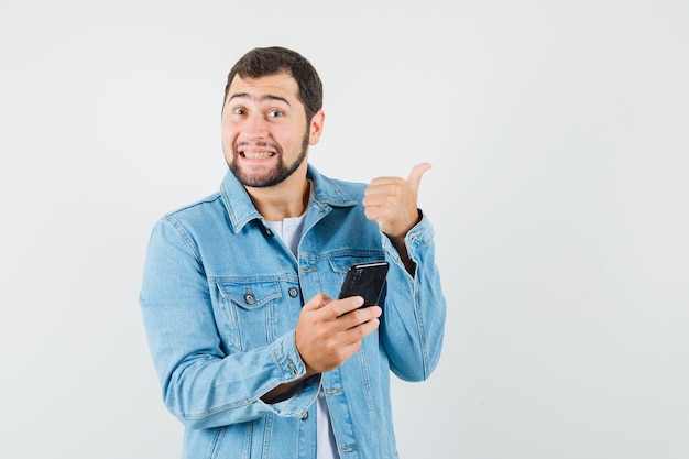 Retro-style man in jacket,t-shirt pointing away while holding phone and looking merry , front view.