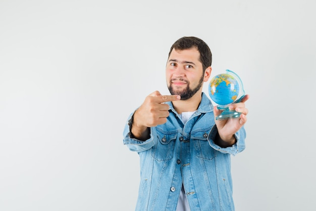 Retro-style man in jacket,t-shirt pointing at mini globe and looking pleased , front view.