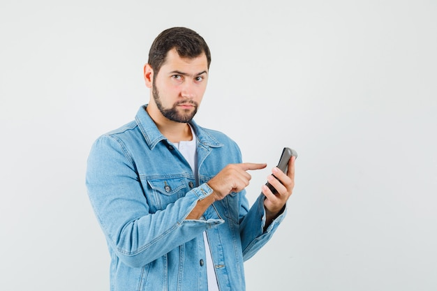 Retro-style man in jacket,t-shirt preparing for calling someone and looking ready , front view.