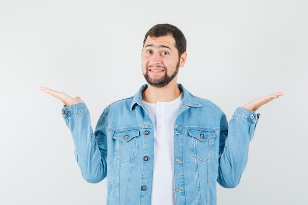 Retro-style man in jacket,t-shirt raising arms for showing something and looking glad , front view.