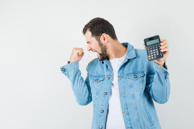 Retro-style man in jacket,t-shirt showing calculator while showing winner gesture and looking happy , front view. space for text
