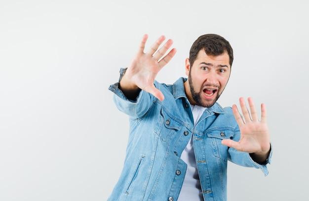 Uomo in stile retrò in giacca, t-shirt che mostra il gesto di rifiuto e sembra spaventato, vista frontale.