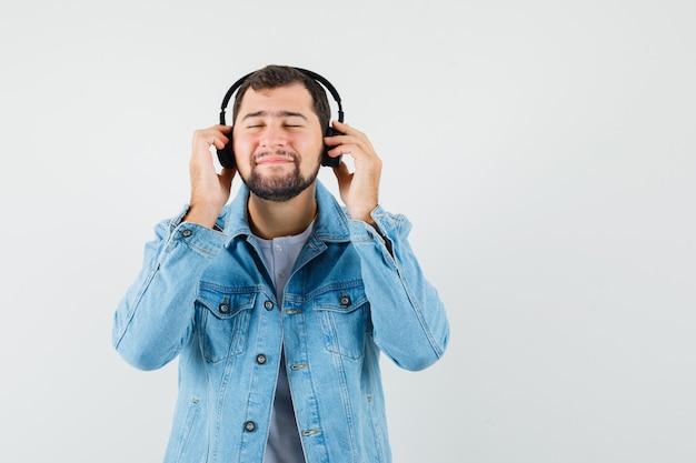 Человек в стиле ретро слушает музыку с наушниками в куртке, футболке и выглядит спокойным. передний план. место для текста