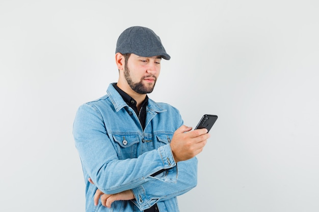Retro-style man looking at phone in jacket,cap,shirt and looking concentrated. front view.
