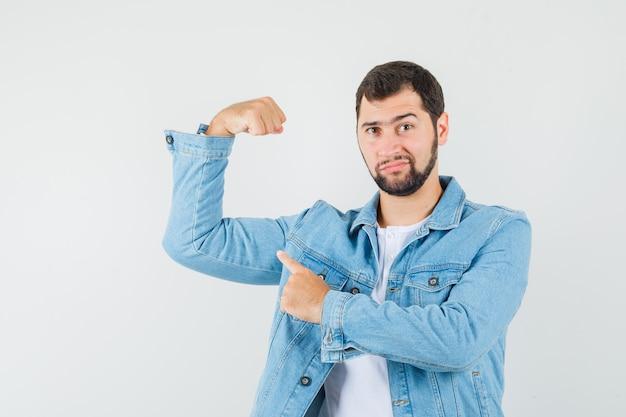 Мужчина в стиле ретро, указывая на мышцы рук в куртке, футболке и самодовольно, вид спереди.