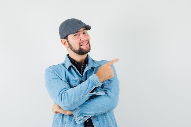 Retro-style man pointing at left in jacket,cap,shirt and looking happy , front view.