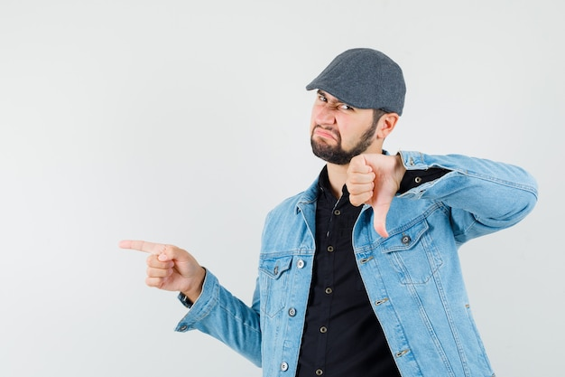 Retro-style man pointing at right while showing thumb down in jacket,cap,shirt and looking upset. front view.