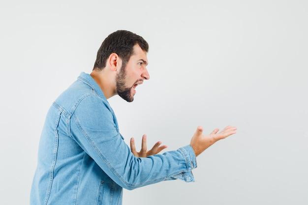 레트로 스타일의 남자는 재킷, 티셔츠에 공격적인 방식으로 손을 올리고 화가 찾고 있습니다.
