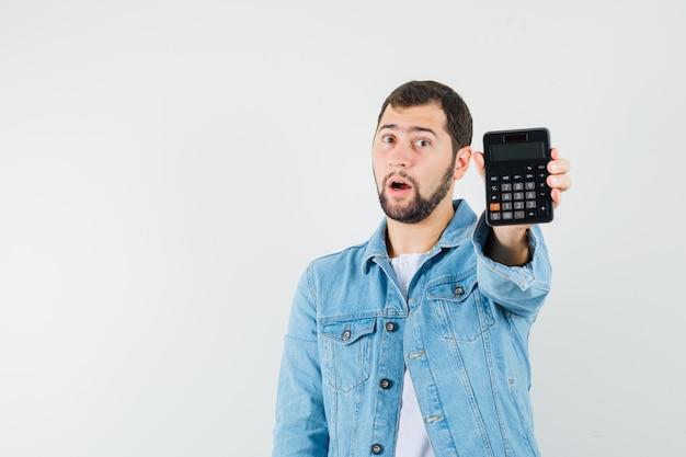ジャケット、tシャツで電卓を表示し、驚いたように見えるレトロなスタイルの男、正面図。テキスト用のスペース