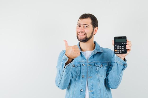 ジャケット、tシャツ、楽観的な正面図で親指を表示しながら電卓を表示するレトロなスタイルの男。テキスト用のスペース
