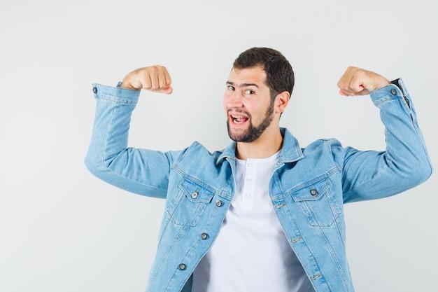Мужчина в стиле ретро показывает мышцы рук в куртке, футболке и выглядит веселым. передний план.
