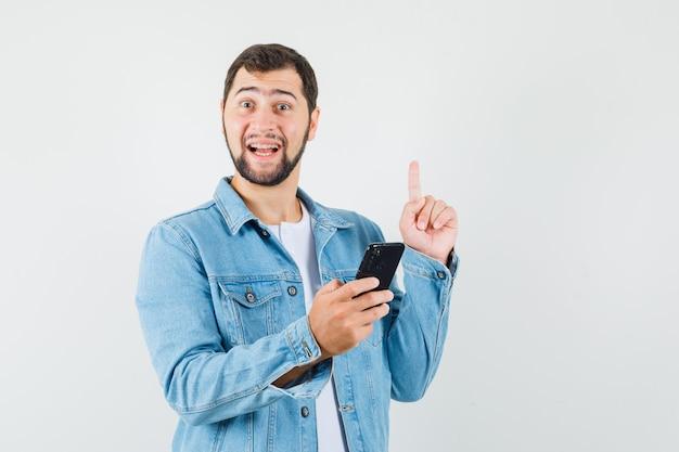 복고풍 스타일의 남자 재킷, 티셔츠에 자신의 전화를 들고 희망, 전면보기를 보면서 새로운 아이디어 제스처를 보여주는.