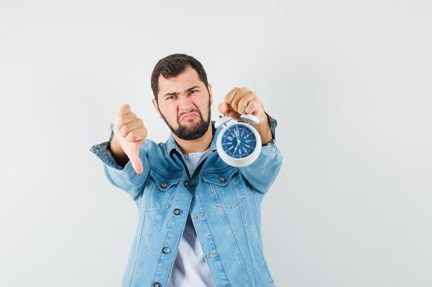 Человек в стиле ретро показывает большой палец вниз, держа часы в куртке, футболке и недоволен, вид спереди.