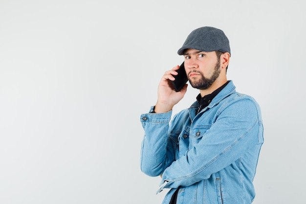 Retro-style man talking on phone in jacket,cap,shirt and looking careful. front view. space for text