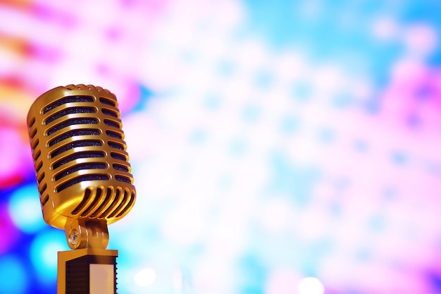 Retro style microphone on background with backlight. vintage silver microphone for sound, music, karaoke. speech broadcast equipment. live pop, rock musical performance. selective focus