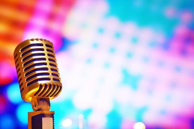 バックライト付きの背景にレトロなスタイルのマイク。サウンド、音楽、カラオケ用のヴィンテージシルバーマイク。音声放送機器。ライブポップ、ロックミュージカルパフォーマンス。セレクティブフォーカス